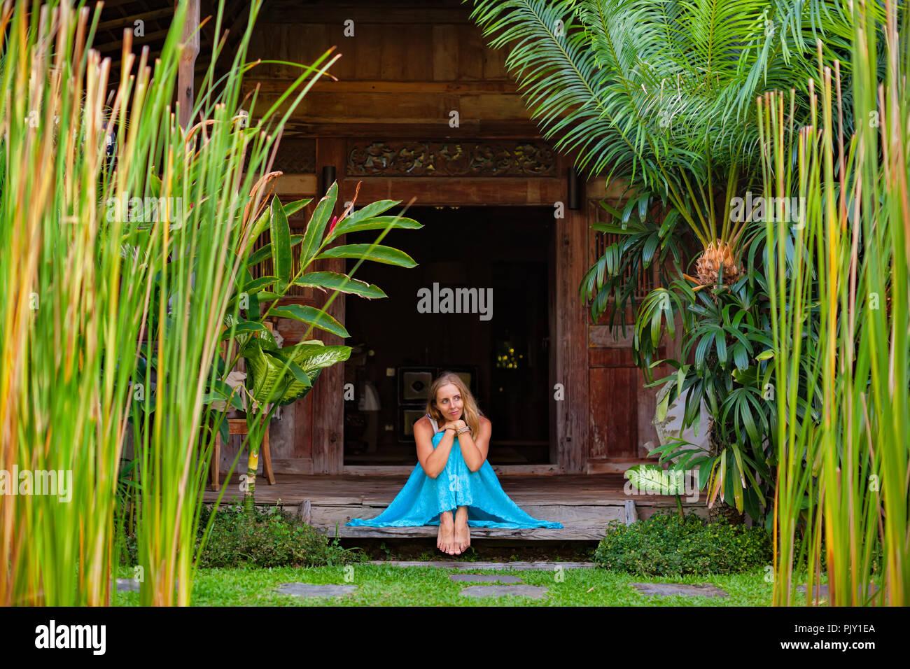 Attractive girl sit on open-air veranda of wooden bungalow, enjoying beautiful tropical garden view. Young woman relaxing in luxury villa Stock Photo