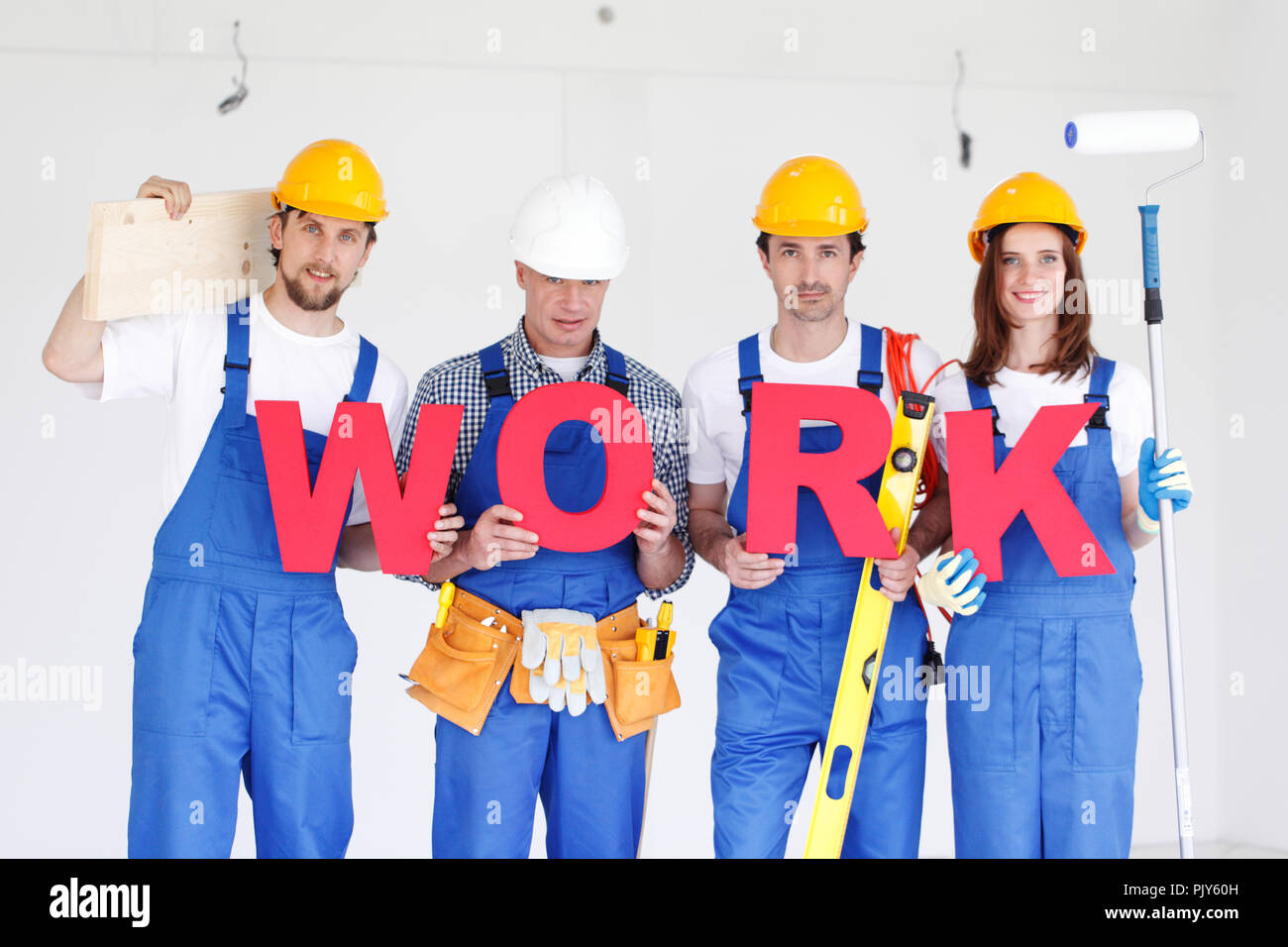Group of workmen with word WORK and tools indoors - Stock Image