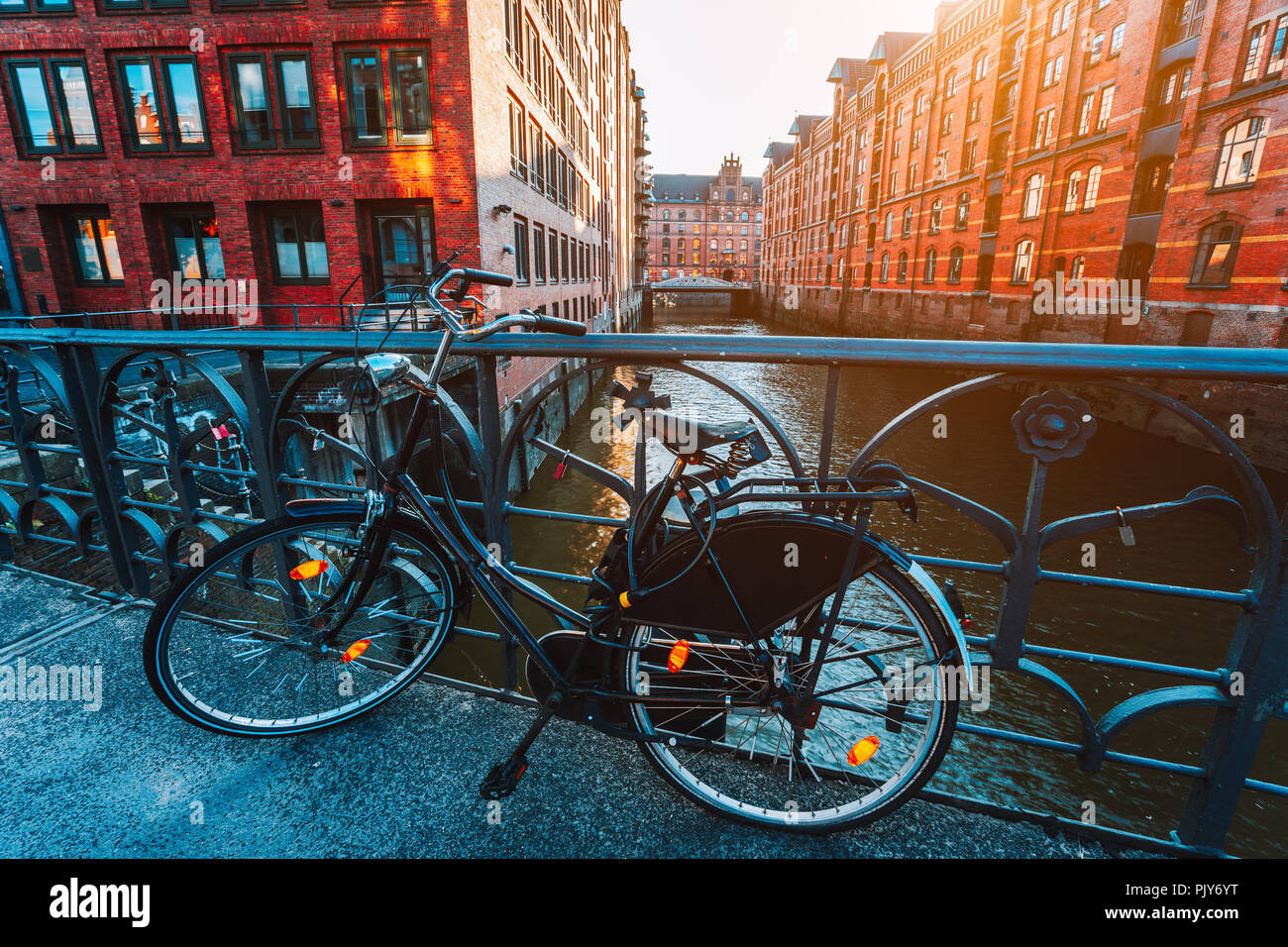 Old bicycle parked against iron hand railing on bridge in Hamburg warehouse district Stock Photo