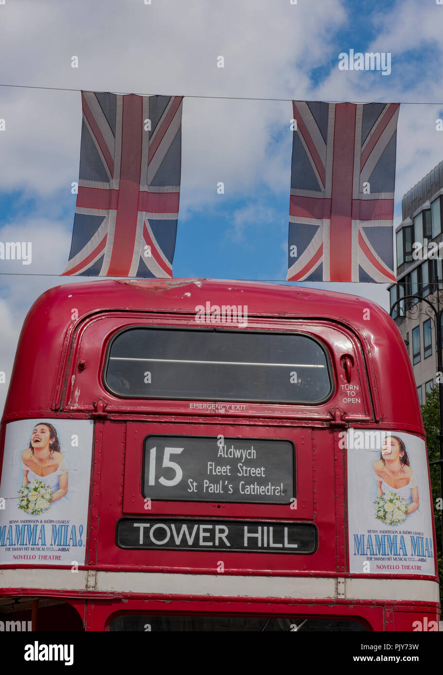 a traditional red double decker London bus with tower hill on the destination board with two union flags or union jacks flying above it. - Stock Image