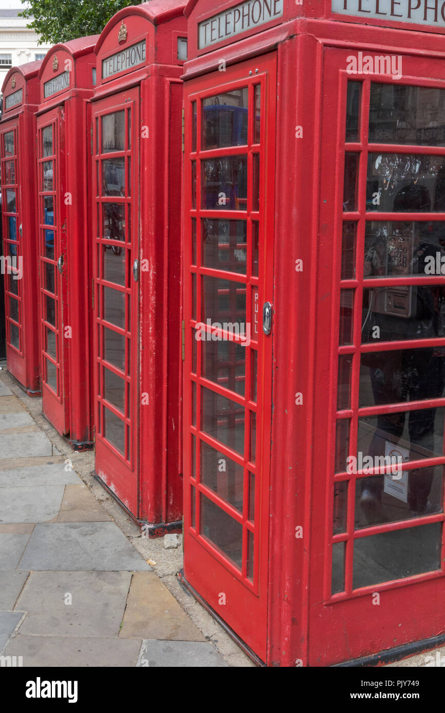 a row of traditional heritage red call or telephone boxes in central London. - Stock Image
