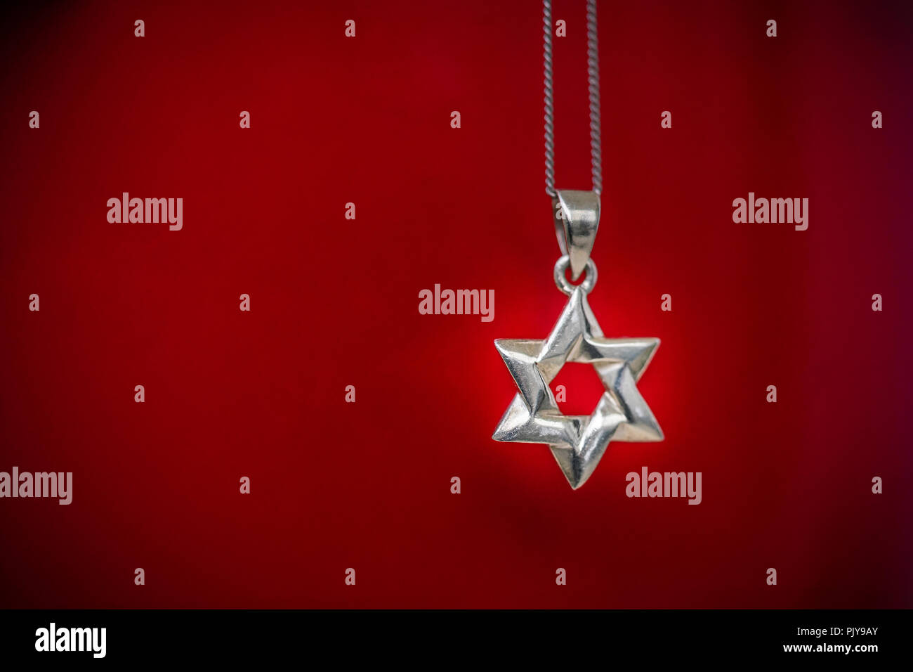 Silver necklace with a silver Star of David pendant against red background - Judaism concept - Stock Image