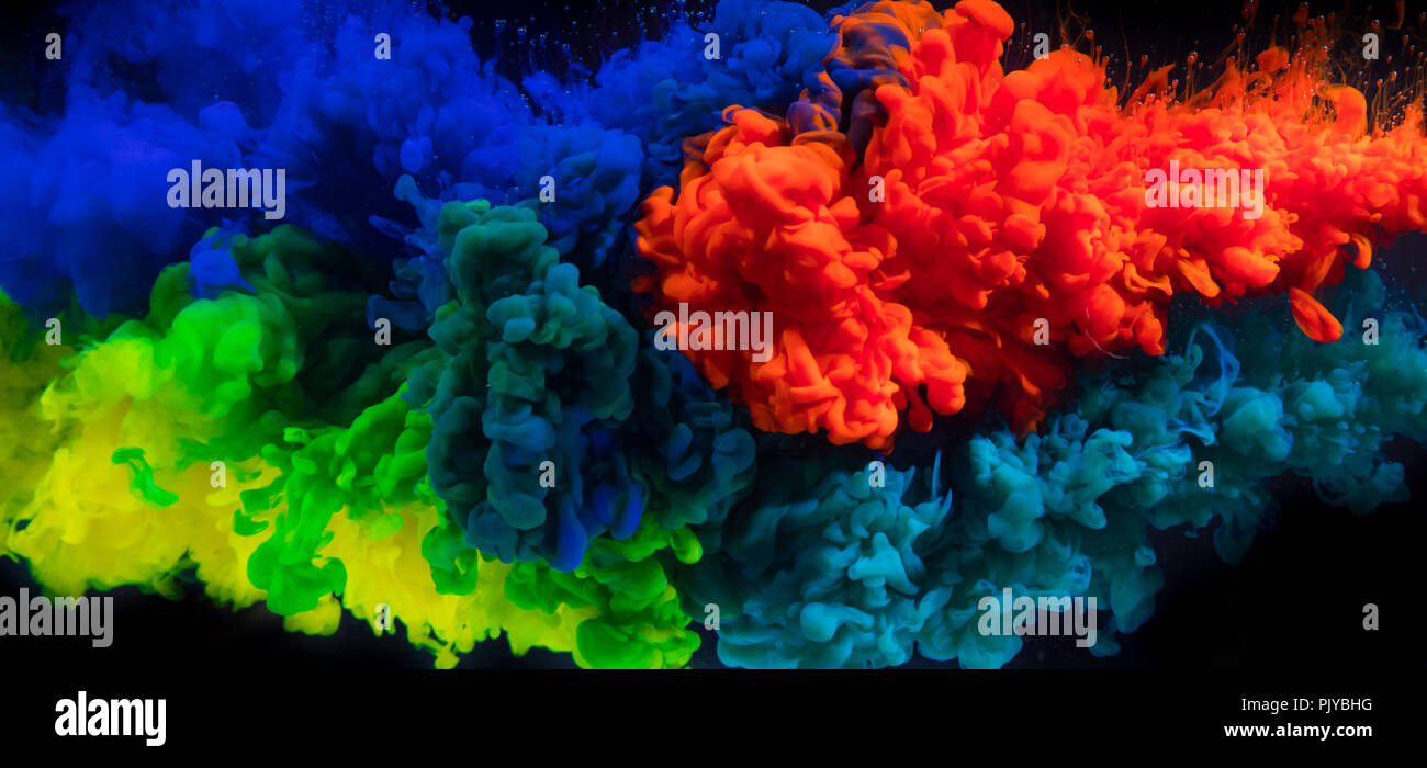 Mix of coloured inks in water on black background. Abstract colored background - Stock Image