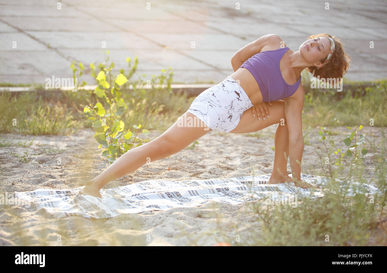 Yoga girl stretching outdoor at sunset.Athletic young white woman in sportswear exercising on fitness program for strong health.Healthy lifestyle and  - Stock Image