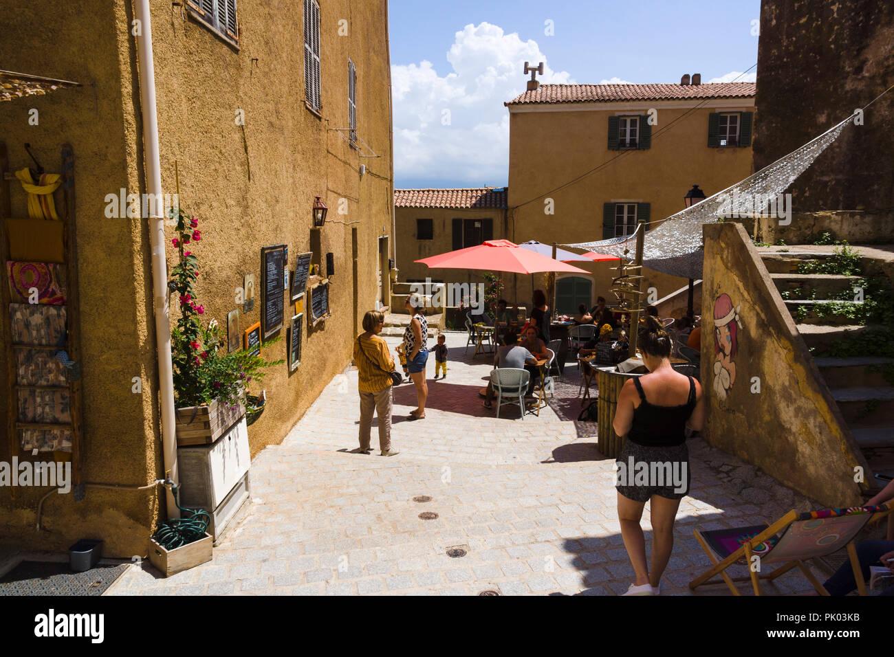 Lunchtime at outdoor restaurant patio in Calvi citadel. Calvi, Corsica, France - Stock Image