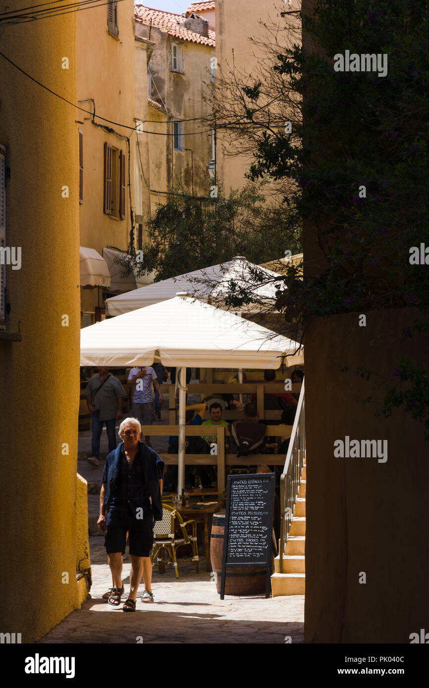 Narrow alley with outdoor restaurant patios in Calvi citadel, Corsica, France - Stock Image