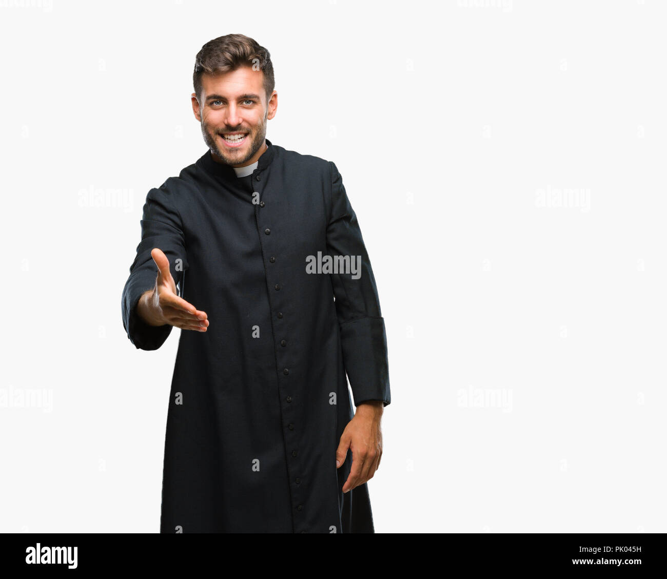 Young catholic christian priest man over isolated background smiling friendly offering handshake as greeting and welcoming. Successful business. - Stock Image