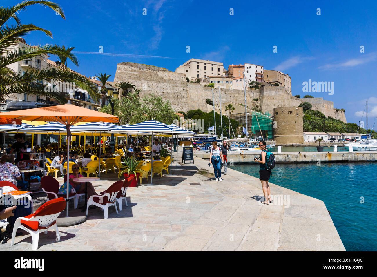 Waterfront restaurants, citadel in background. Calvi, Corsica, France - Stock Image