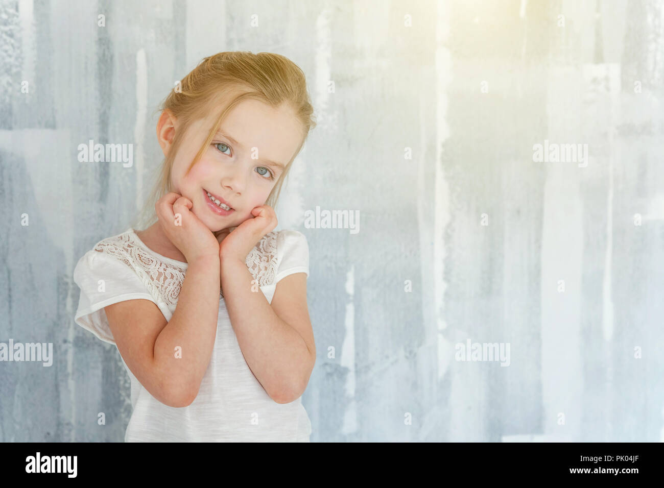 Sweet happy little girl in blank white t-shirt standing against grey textured wall background Childhood, schoolchildren, youth, relax concept Stock Photo