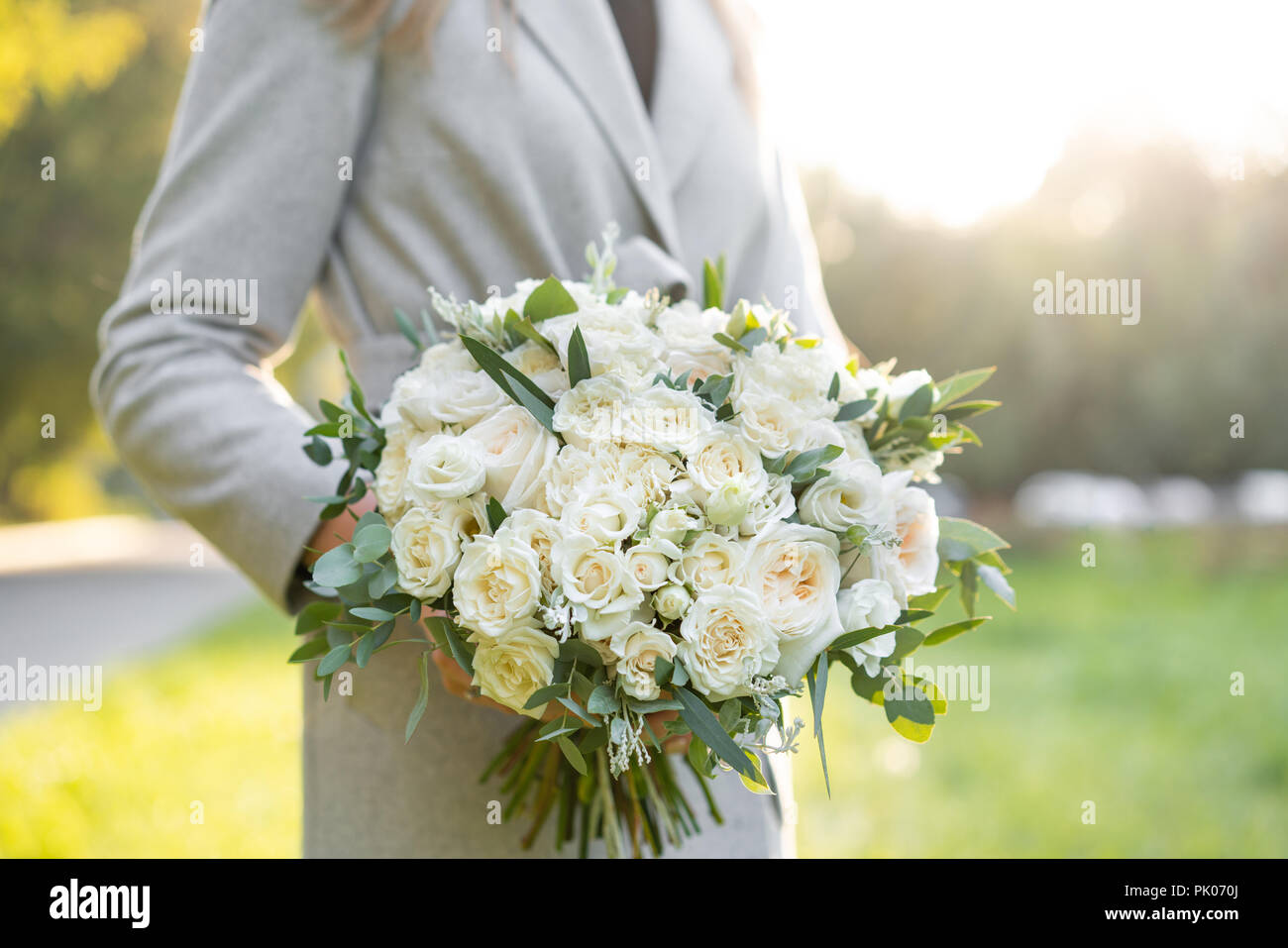 Young girl holding a beautiful spring bouquet flower arrangement young girl holding a beautiful spring bouquet flower arrangement with white flowers bright dawn or sunset sun izmirmasajfo