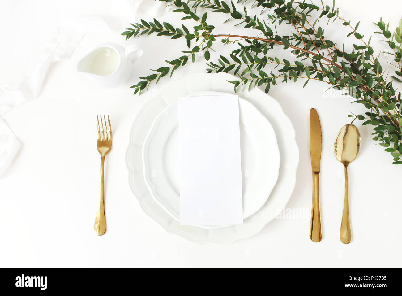 Festive wedding, birthday table setting with golden cutlery, eucalyptus parvifolia branch, porcelain plate, milk and silk ribbon. Blank card mockup. Rustic restaurant menu concept. Flat lay, top view Stock Photo