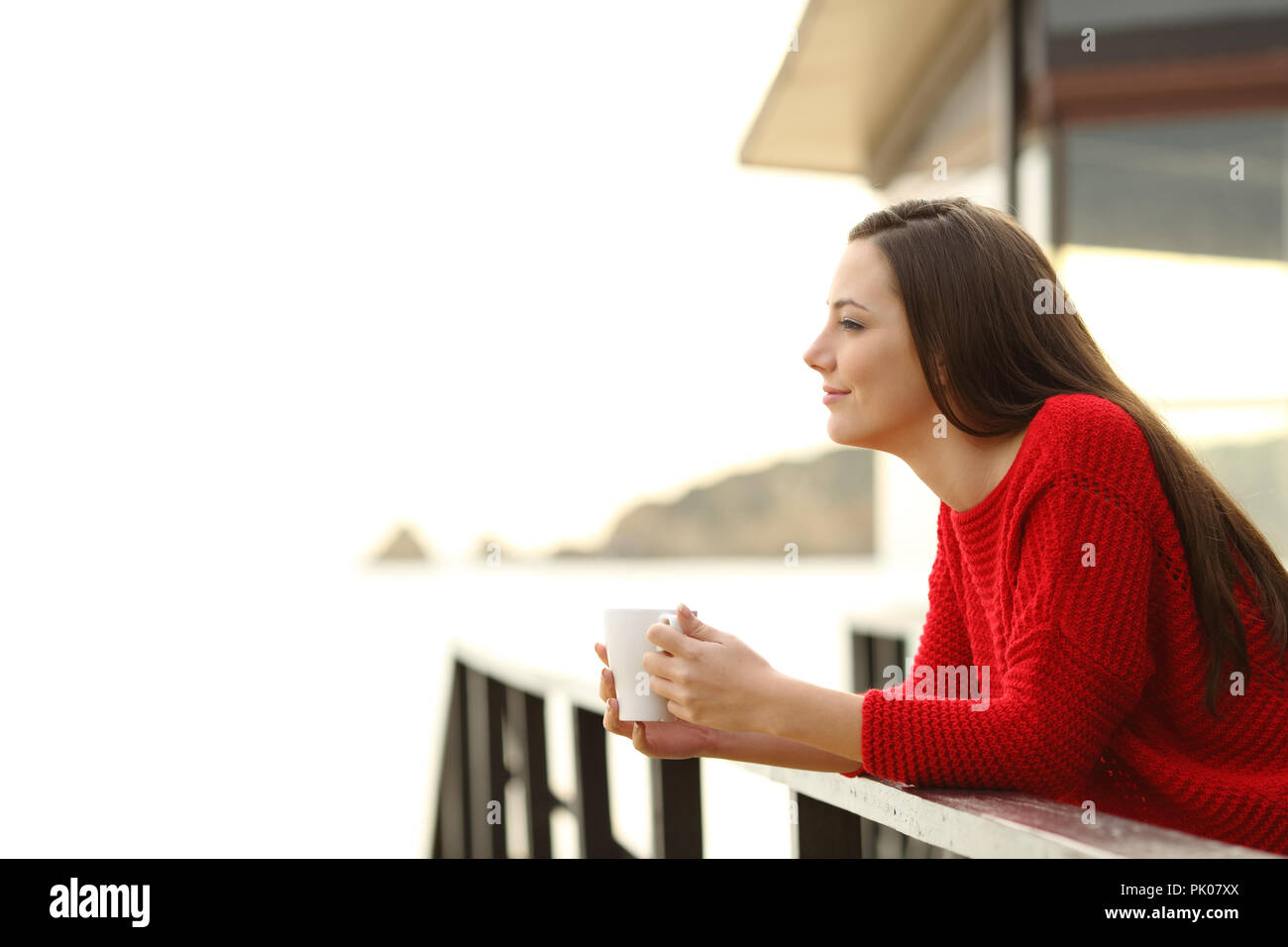 Side view portrait of a relaxed woman contemplating beach views from hotel on the beach - Stock Image