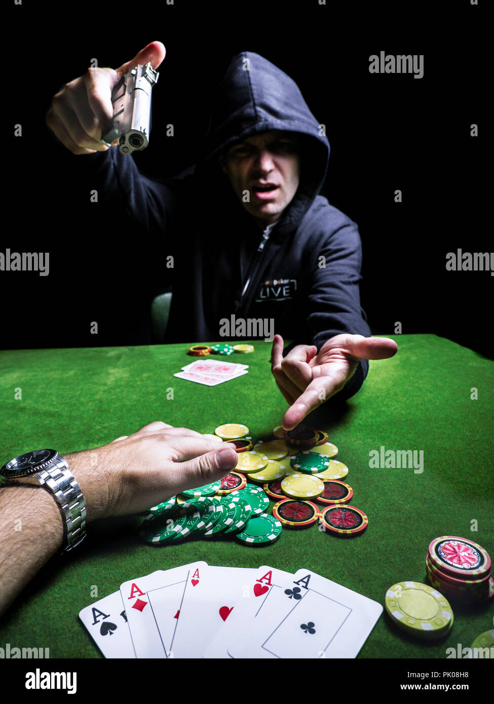 poker player angry pointing a gun handgun cheater cheating card game cards chips hoodie - Stock Image