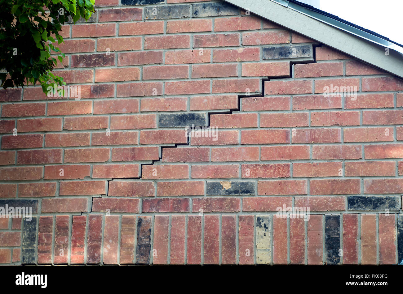 Brick and mortar separation on a red brick wall.This is typically due to a sinking foundation in a structure. - Stock Image