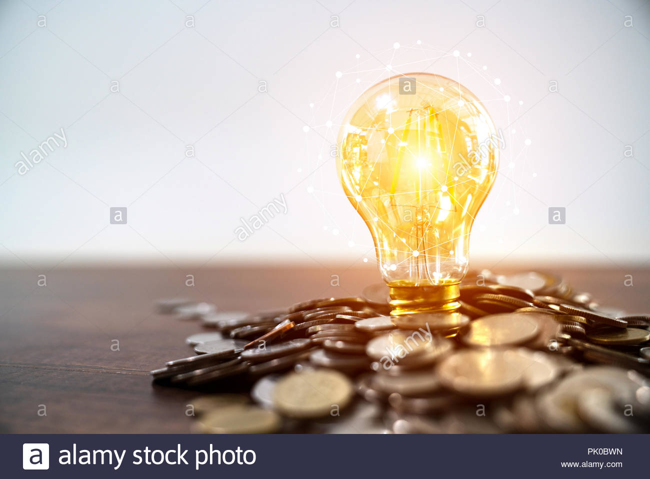 Light bulb and stack of coins in concept of savings and money growing or energy save - Stock Image