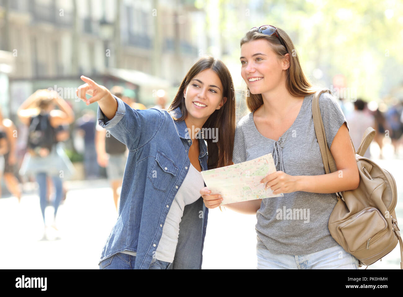 Happy girl helping to a tourist who asks direction in the street - Stock Image