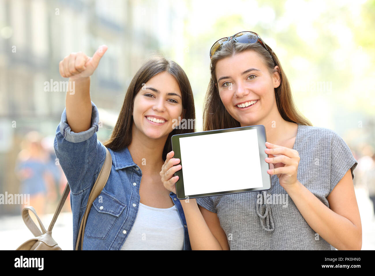 Front view portrait of a positive friends showing a blank tablet screen in a street - Stock Image