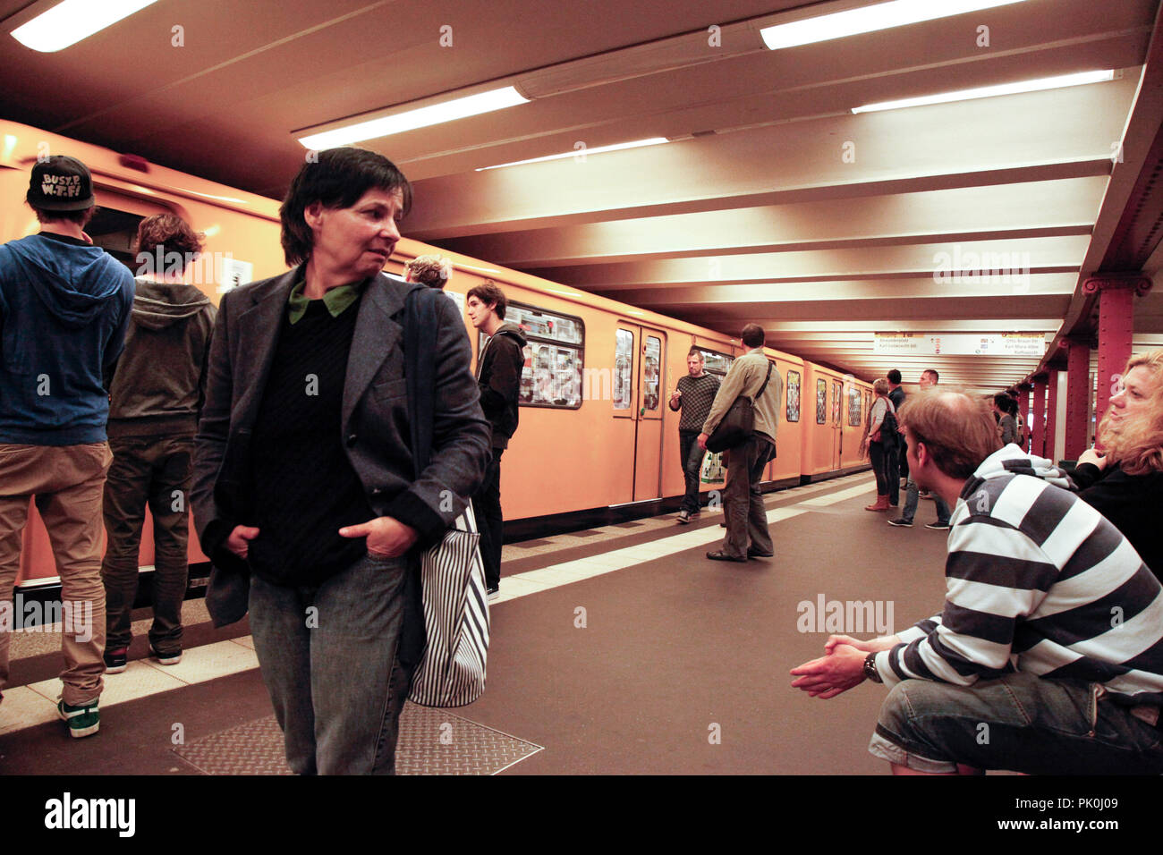 People at the underground Alexanderplatz metro station in Berlin, Germany load and unload passengers - Stock Image