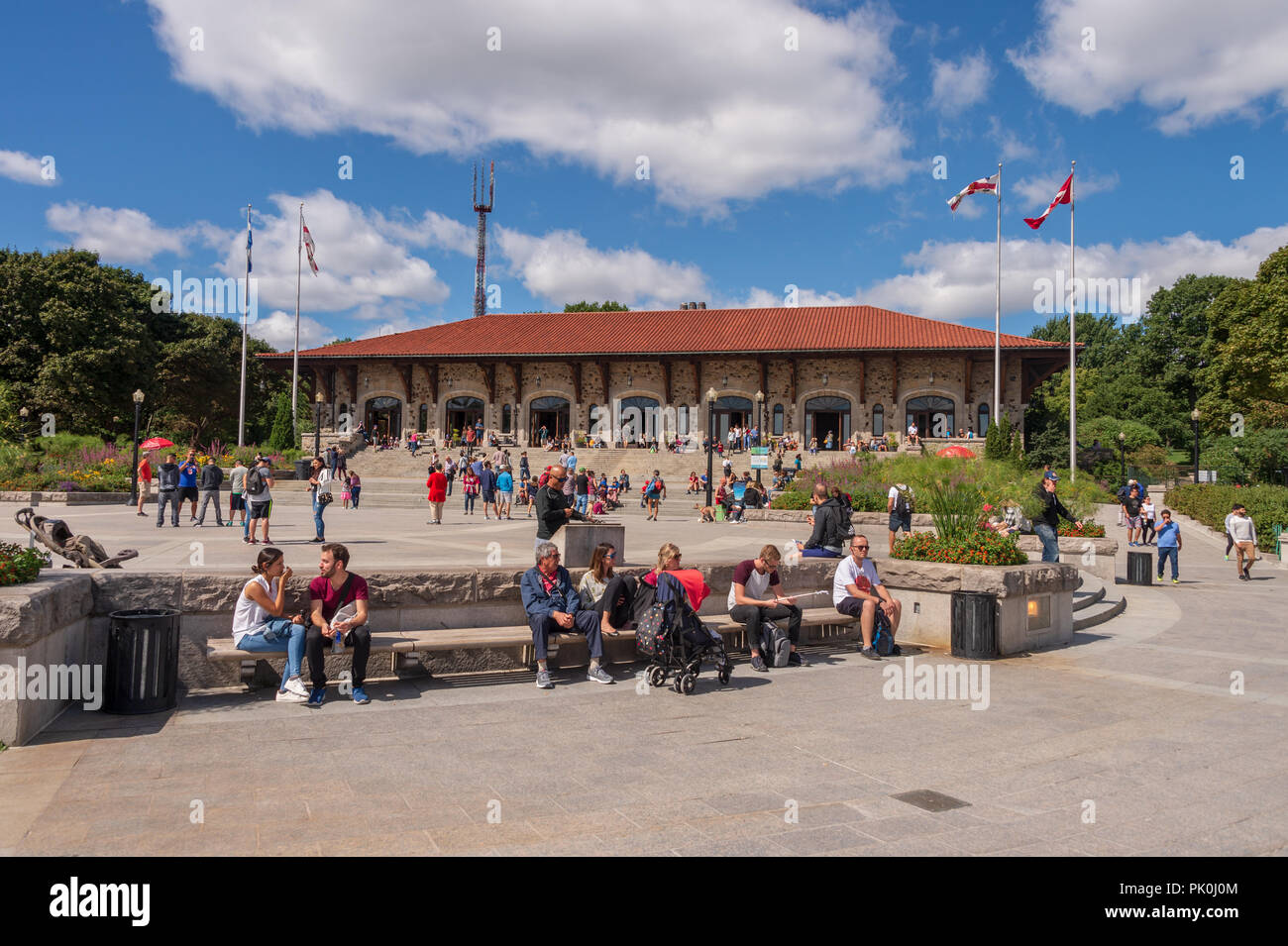 Montreal, CA - 8 September 2018: Tourists enjoy a warm summer day at the Kondiaronk Belvedere in front of the Chalet du Mont Royal. - Stock Image