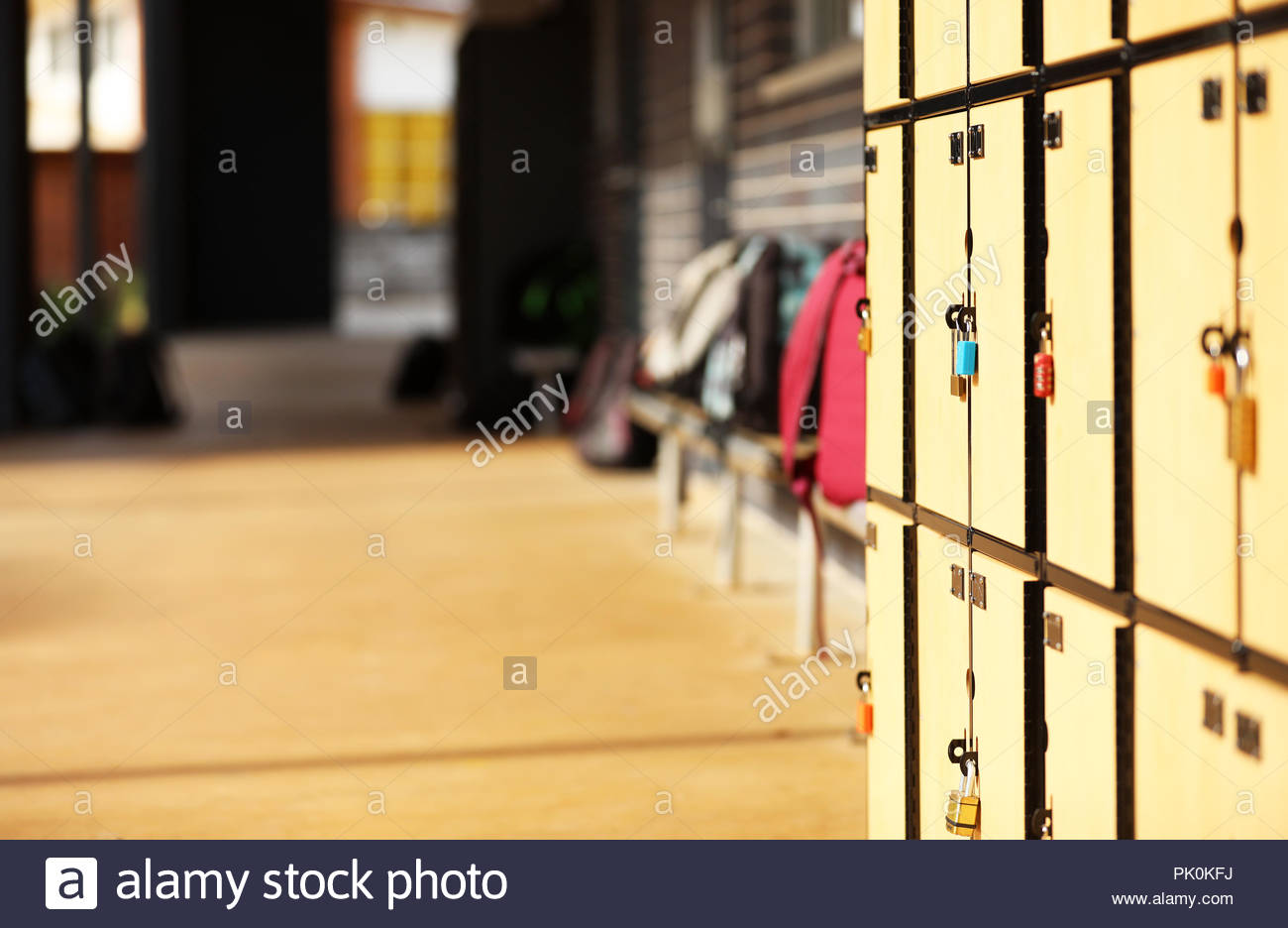 school yard lockers locked with bags backpacks in the background. Education Educational facility institution with classroom and student school bags. - Stock Image