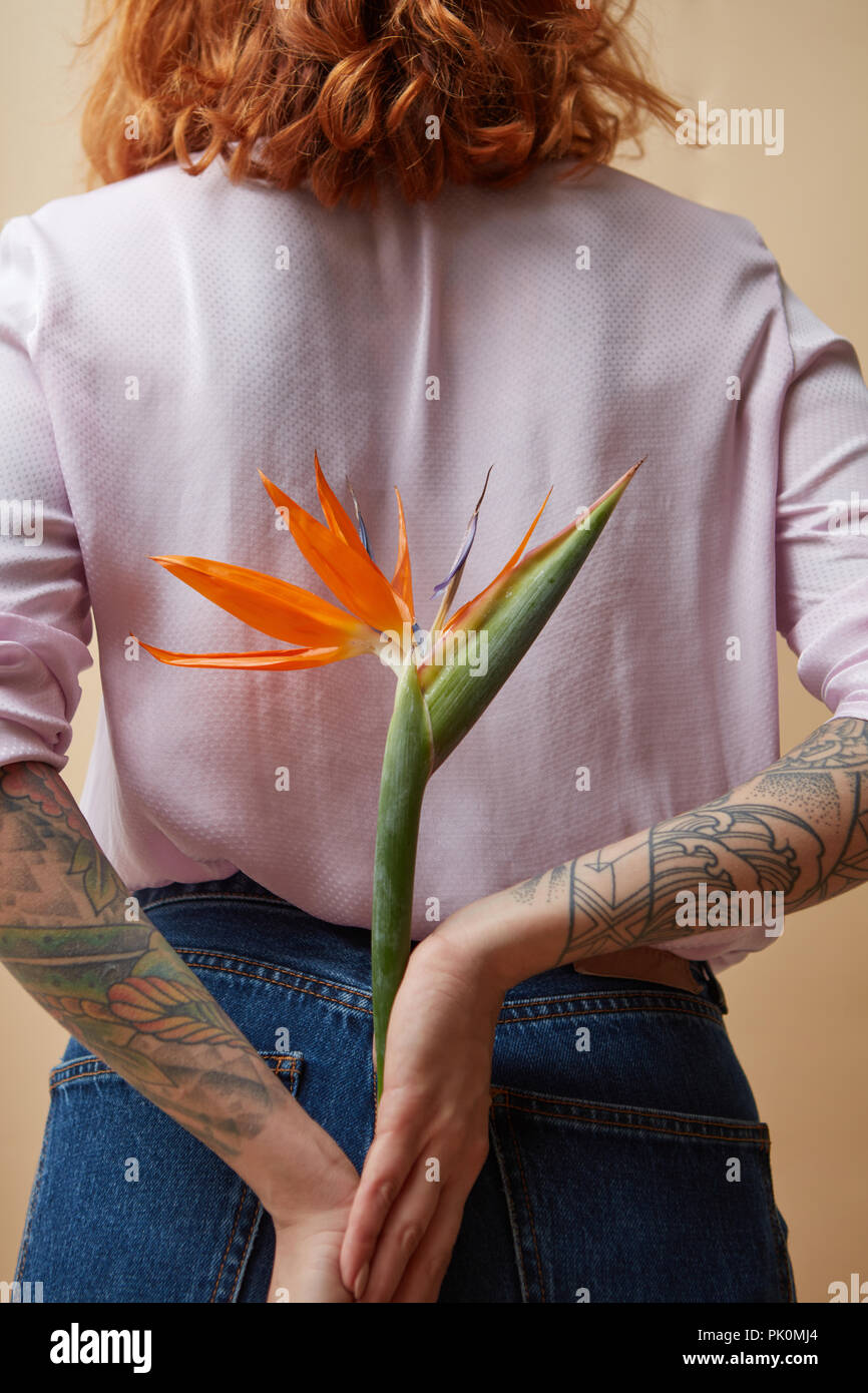 Girl In The Pink Shirt Holding Flowers In Her Tattoo Hands Behind
