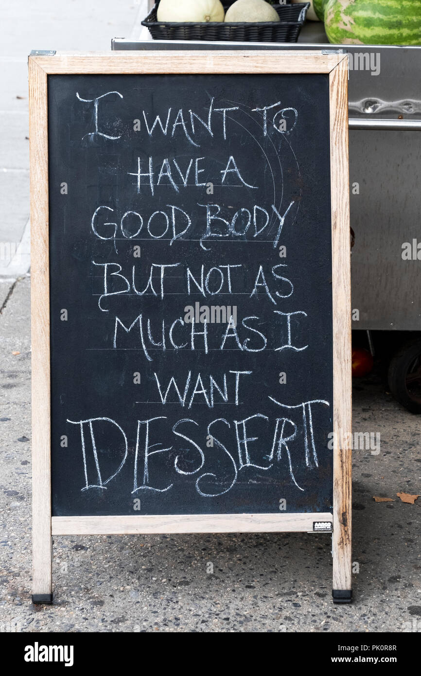 A funny sign outside a coffee shop in Astoria, Queens, New York reading 'I want to have a good body but not as much as I want dessert.' - Stock Image