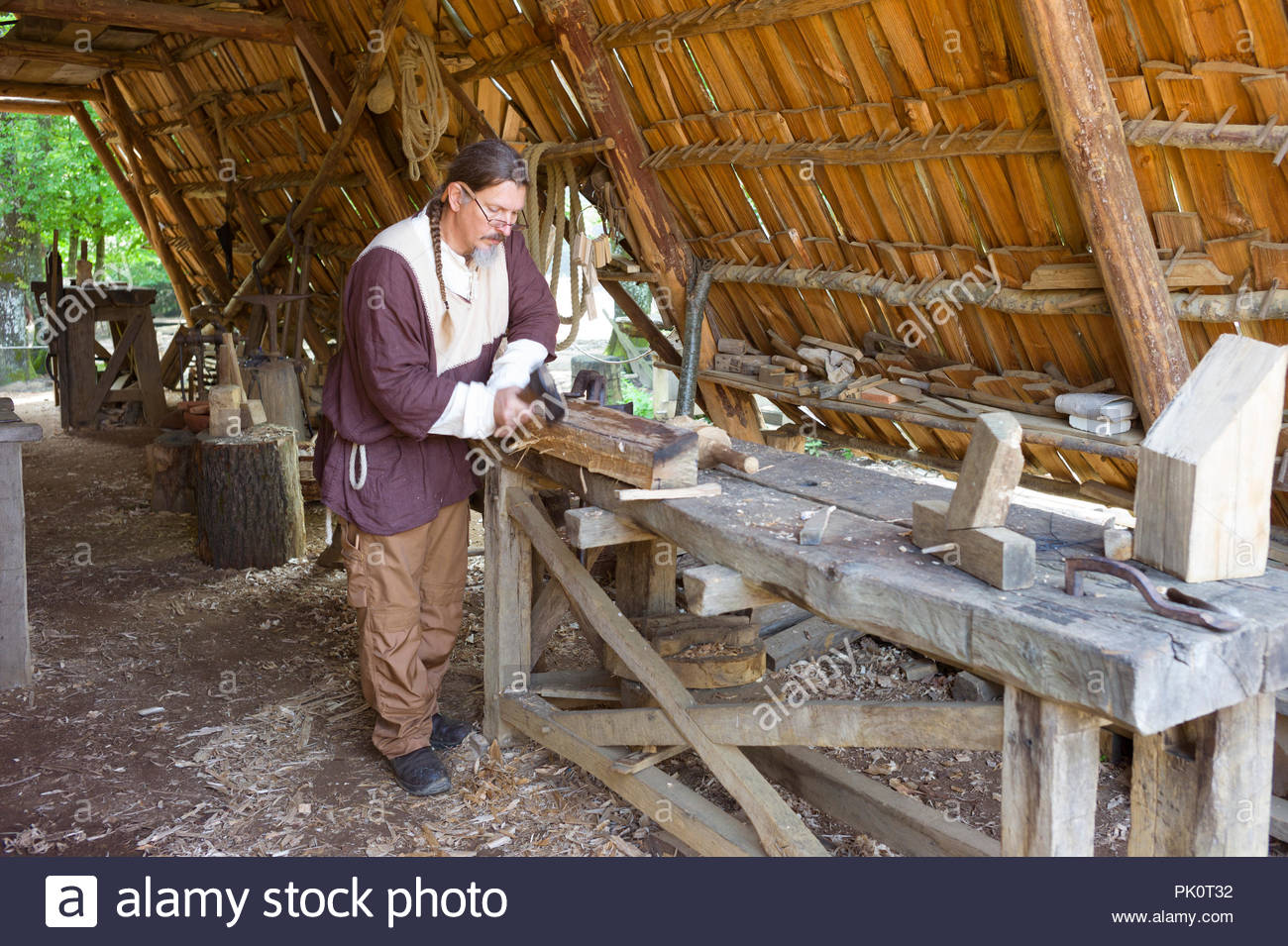 A Carpenter working at Gudelon Castle, Burgundy, France. The castle is being built entirely using medieval tools and building methods. Stock Photo