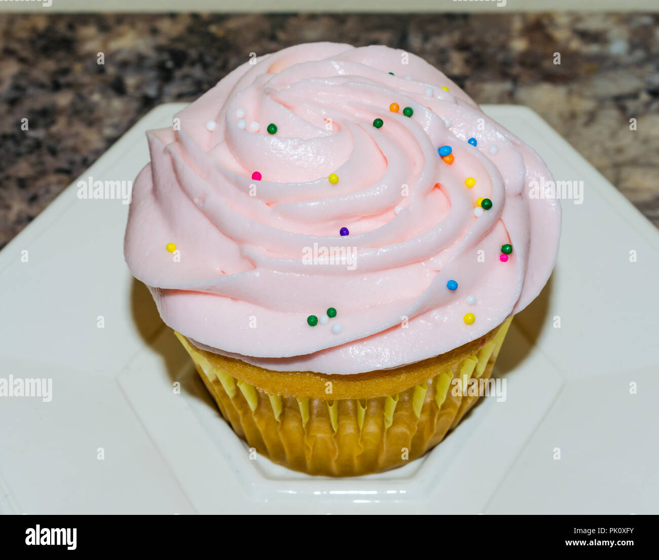 Light pink butter cream frosting swirled on top of fresh homemade cupcake. Colorful candy sprinkles sprinkled on top. Delicious sweet treat for party. - Stock Image