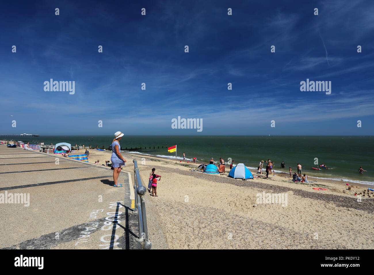 A woman standing on the promenade in front of beach huts gazes out over the beach at Southwold, Suffolk, UK during the heatwave of 2018. - Stock Image