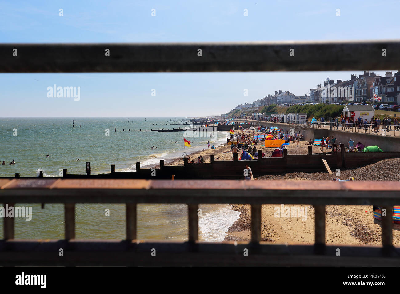 The beach at Southwold, Suffolk, UK, looking through railings on the promenade. - Stock Image