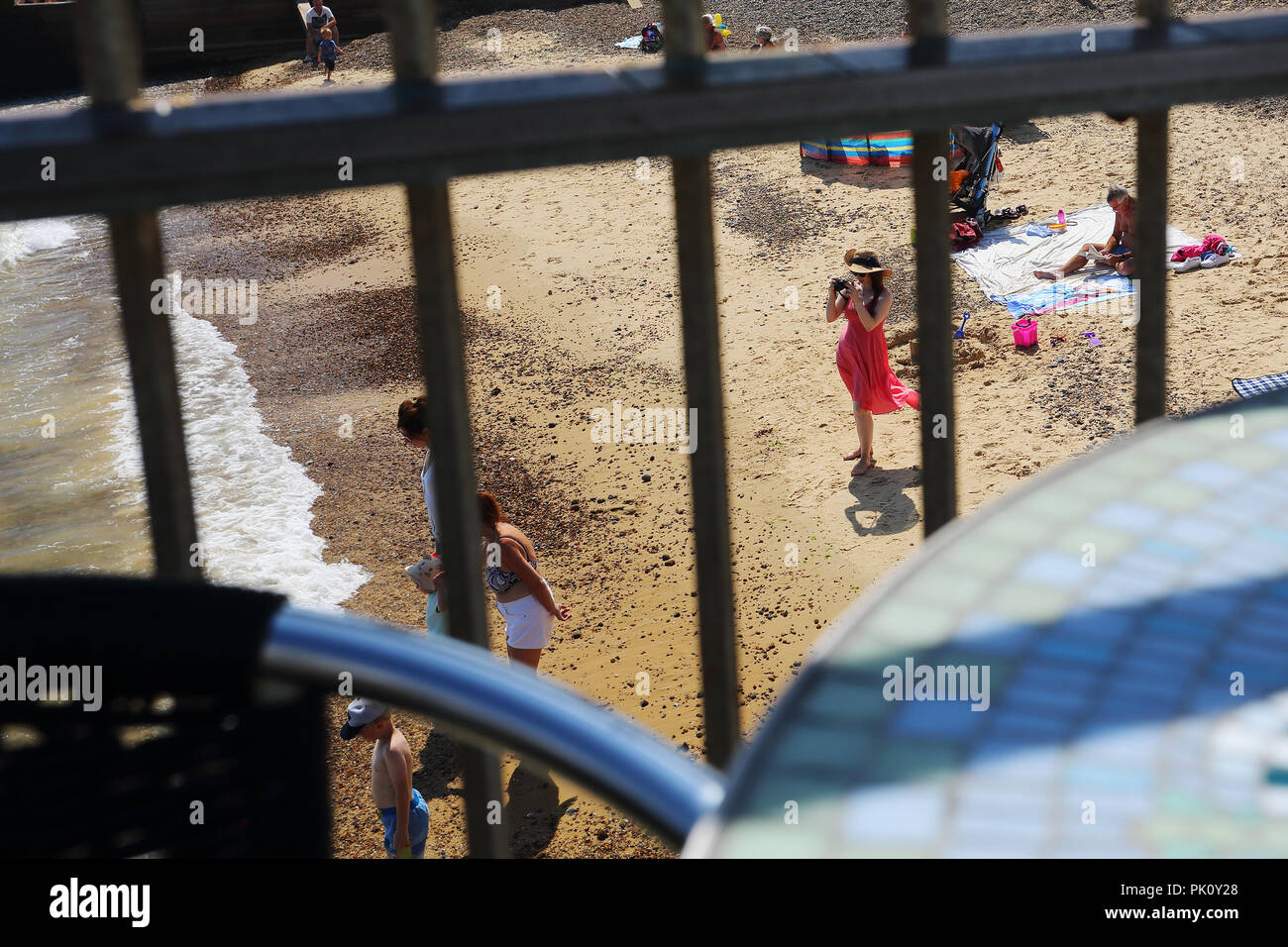 A young woman in a pretty dress takes photographs of holidaymakers on  the beach at Southwold, Suffolk, UK during the heatwave of 2018. - Stock Image