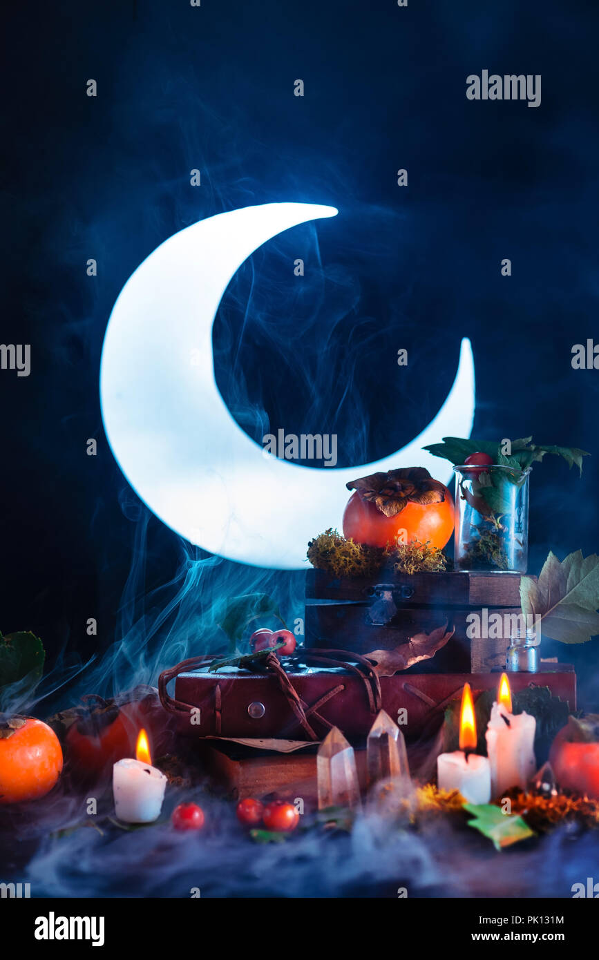Halloween persimmon with shining full Moon. Witch or wizard workplace with burning candles. Spooky still life concept on a dark background with copy s - Stock Image