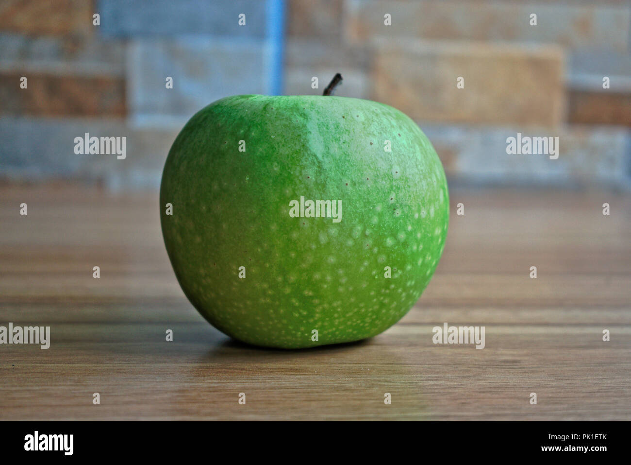 Closeup of a green apple on a wooden table - Stock Image