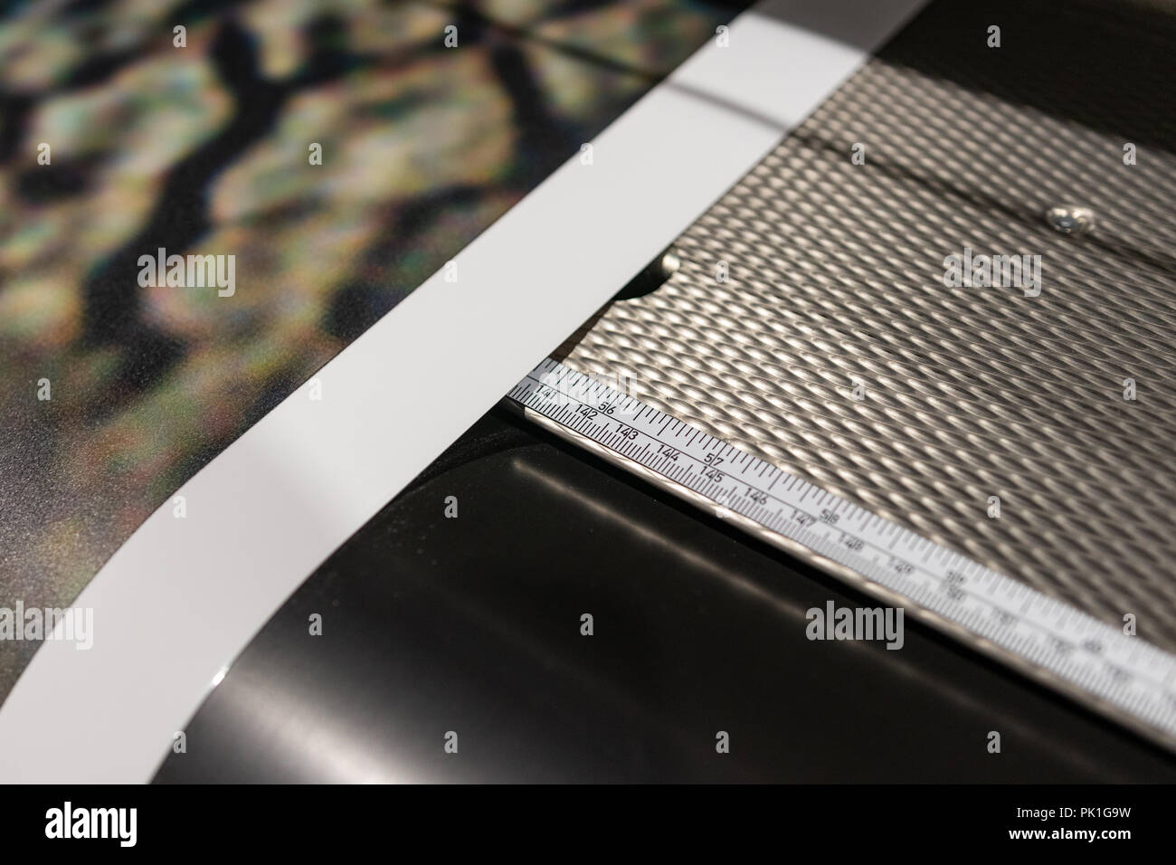 Professional printing facility, details of paper feed and ruler for precision cuts. - Stock Image