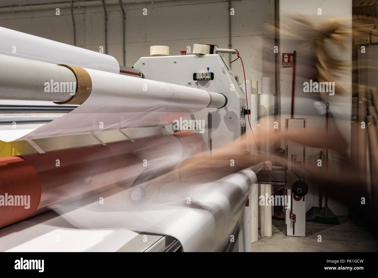 Big professional printing laminator, armed with large red rolls of glossy paper and smaller tubes of transparent film. - Stock Image