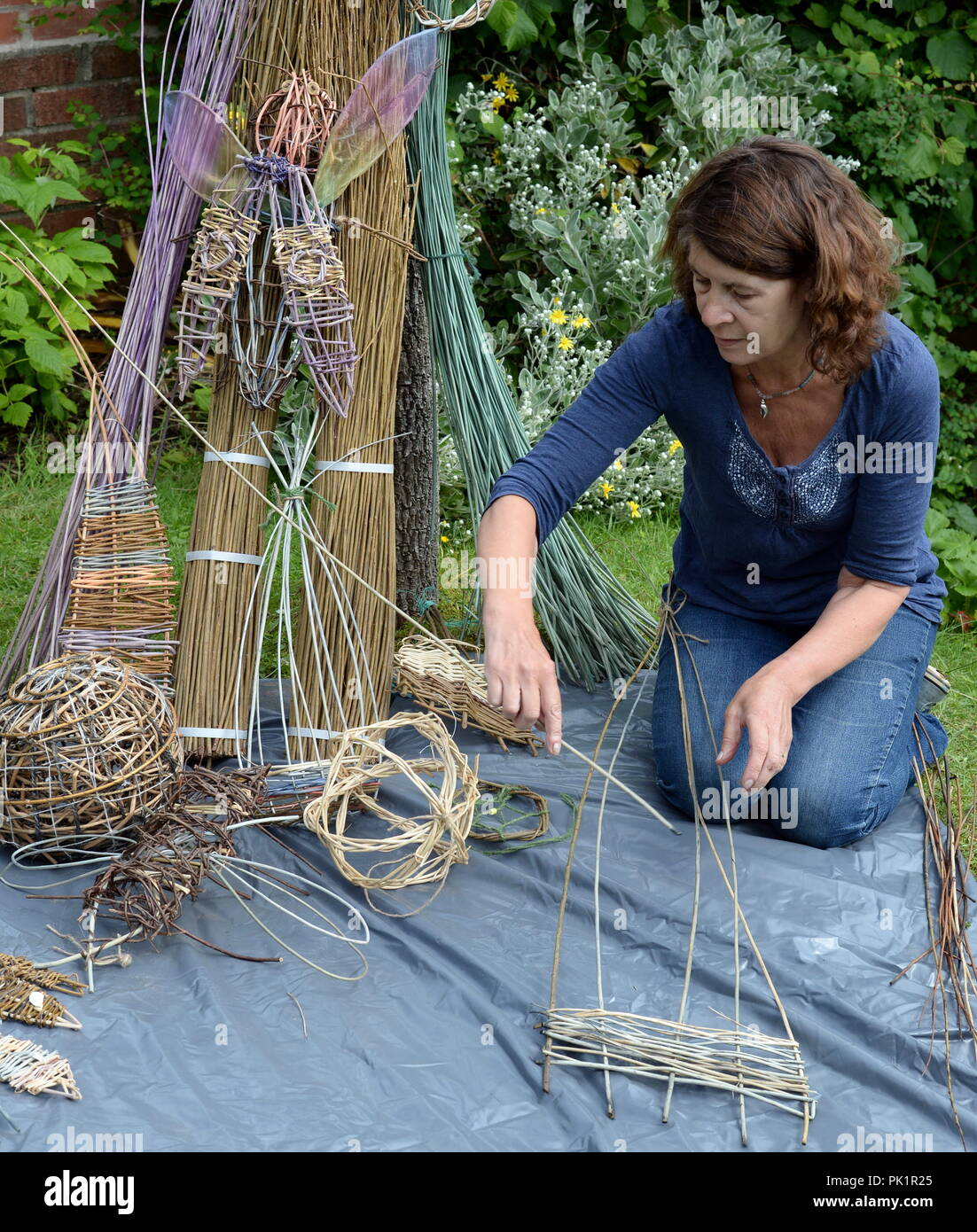 Small Willow sculptures are laid out in front of a variety of wicker stems with artist Sara Holden - Stock Image