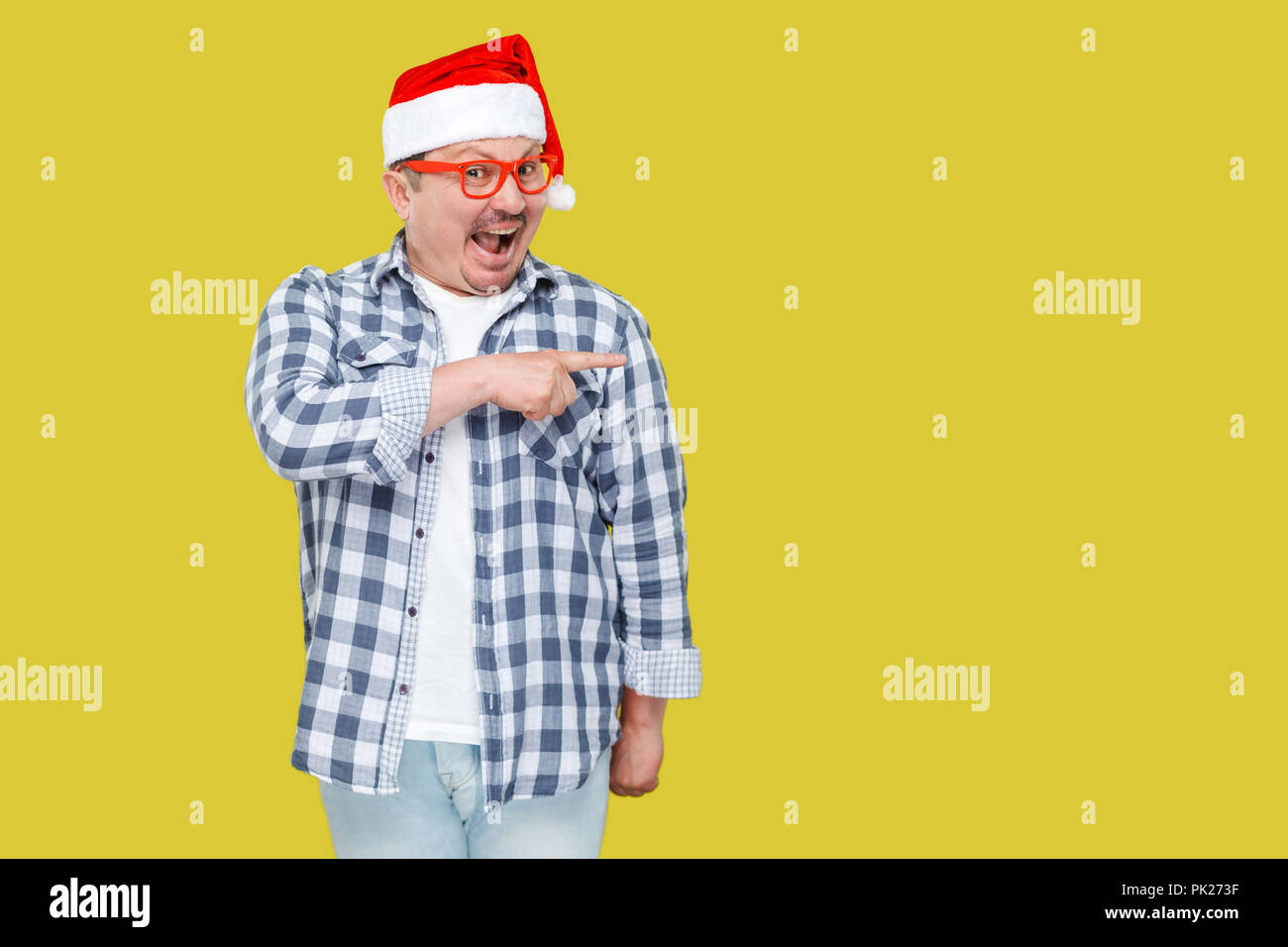 Positive middle aged man in red new year santa cap and casual style, standing, pointing finger to empty copy space and with suprised face, looking at  Stock Photo