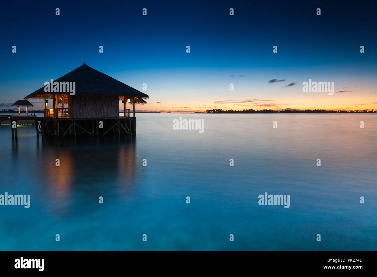 Maldivian Tropical Sunset with Bamboo Villa and Lights on smooth Ocean - Stock Image