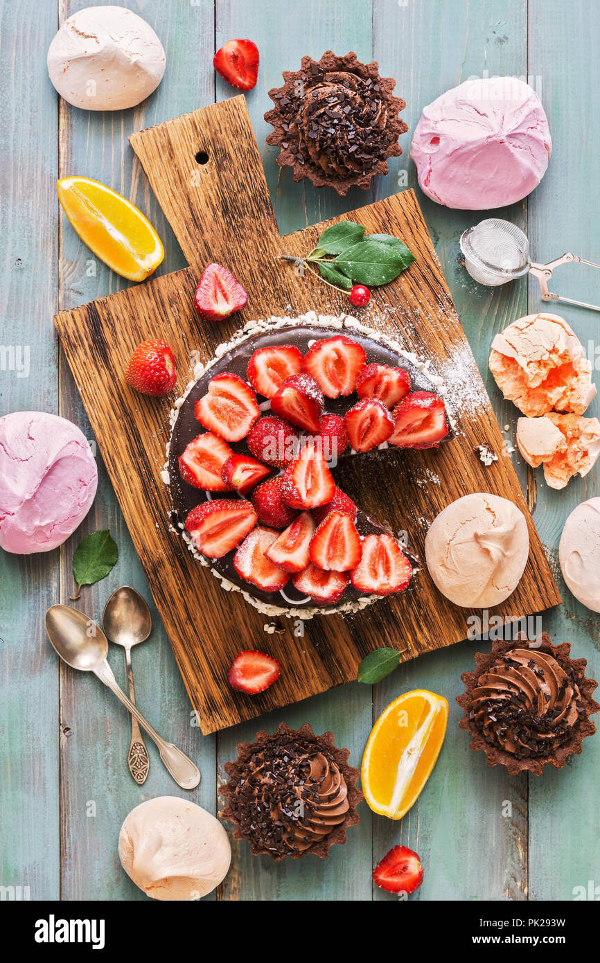 A variety of festive sweets-cupcakes, chocolate cake with strawberries, meringue on a green wooden rustic background. Flat lay. - Stock Image