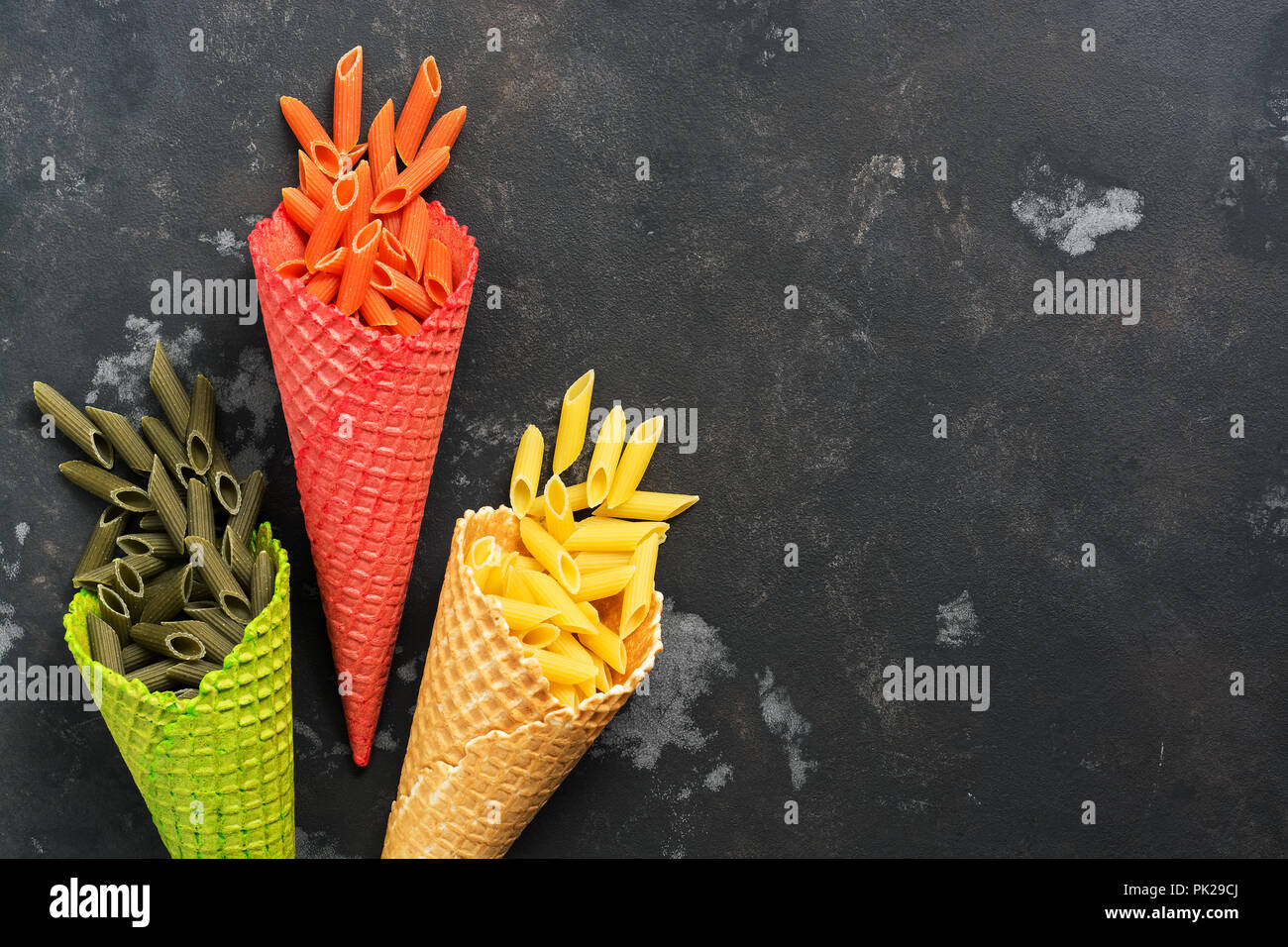 Colored pasta. Colored macaroni penne in waffle cones. The concept of nutrition. View from above, flat lay. - Stock Image