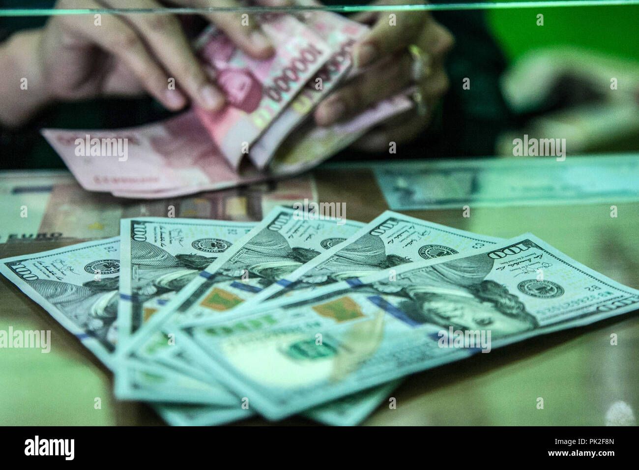 Medan, North Sumatra, Indonesia. 10th Sep, 2018. An employee counts Indonesian 100,000 rupiah banknotes as a bundle of U.S. one-hundred dollar banknotes sits on a counter at a currency exchange store in Medan on Sept 10, 2018, Indonesia. As Aug. 15's policy decision approaches, Bank Indonesia finds itself under pressure to raise the benchmark rate again even after increasing it by a combined 100 basis points since mid-May to stem a slide in the currency, where estimates that the Rupiah exchange rate will stabilize in the range of 14,835 rupiah per US dollar on today. (Credit Image: © Iv Stock Photo