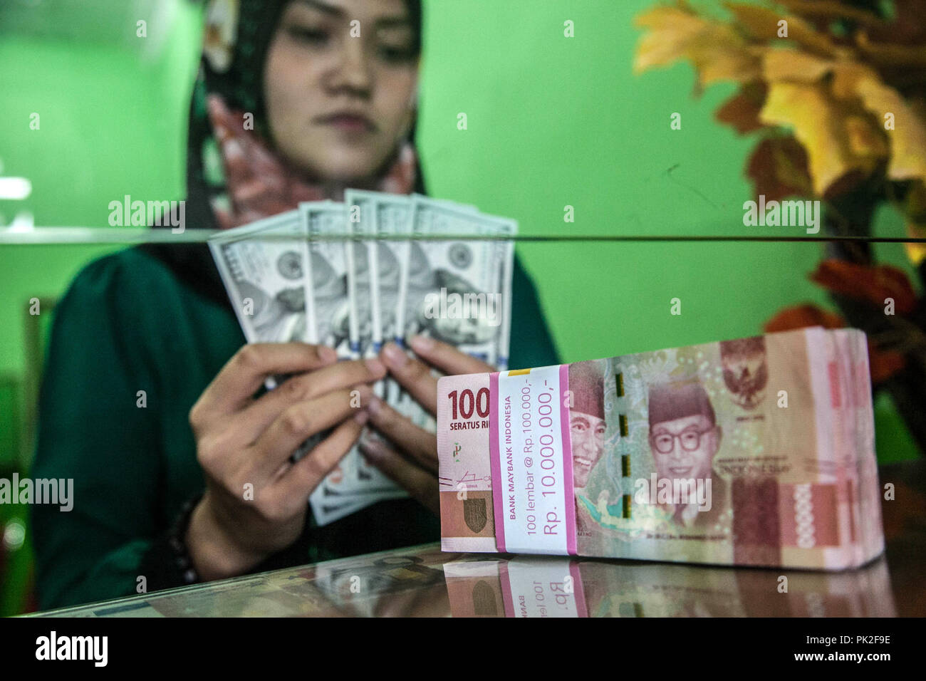 Medan, North Sumatra, Indonesia. 10th Sep, 2018. An employee counts U.S. one-hundred dollar banknotes as a bundle of Indonesian 100,000 rupiah banknotes sits on a counter at a currency exchange store in Medan on Sept 10, 2018, Indonesia. As Aug. 15's policy decision approaches, Bank Indonesia finds itself under pressure to raise the benchmark rate again even after increasing it by a combined 100 basis points since mid-May to stem a slide in the currency, where estimates that the Rupiah exchange rate will stabilize in the range of 14,835 rupiah per US dollar on today. (Credit Image: © Iv Stock Photo