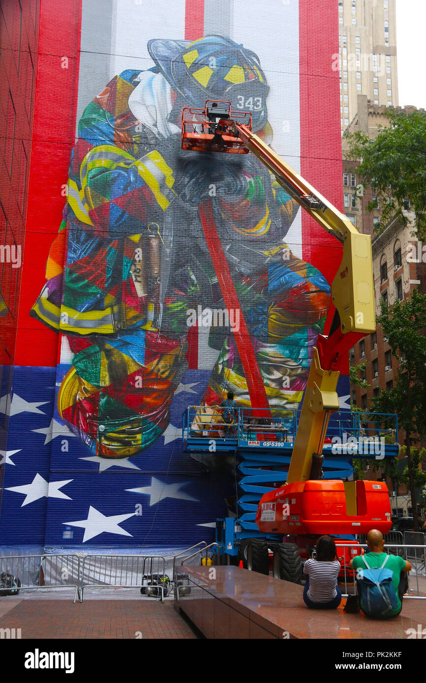 New York City, New York, USA. 10th Sep, 2018. Using a crane finishing touches are made to Brazilian artist Eduardo Kobra's new 9/11 firefighter memorial mural which is painted over 8 stories in Midtown Manhattan. Credit: Nancy Kaszerman/ZUMA Wire/Alamy Live News - Stock Image