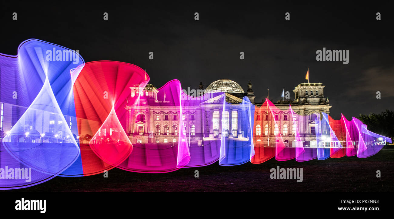Berlin, Germany. 10 September 2018, Berlin: A Berliner draws colourful patterns in the evening sky with a light stick on the meadow in front of the Reichstag. (time exposure) Photo: Paul Zinken/dpa Credit: dpa picture alliance/Alamy Live News - Stock Image