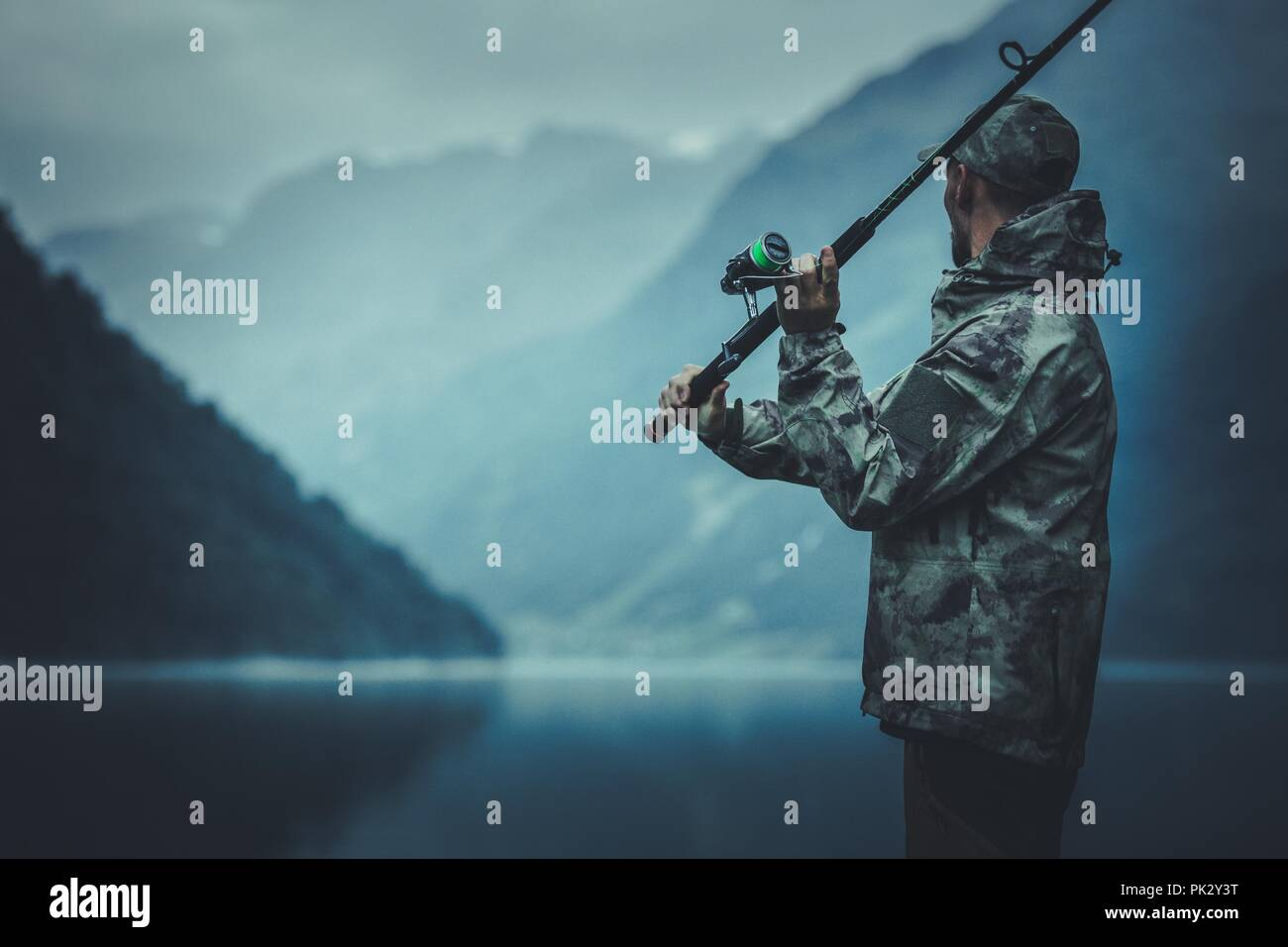 Evening Fly Fishing Time. Caucasian Fisherman with Fishing Rod on the Glacial Lake Shore. - Stock Image