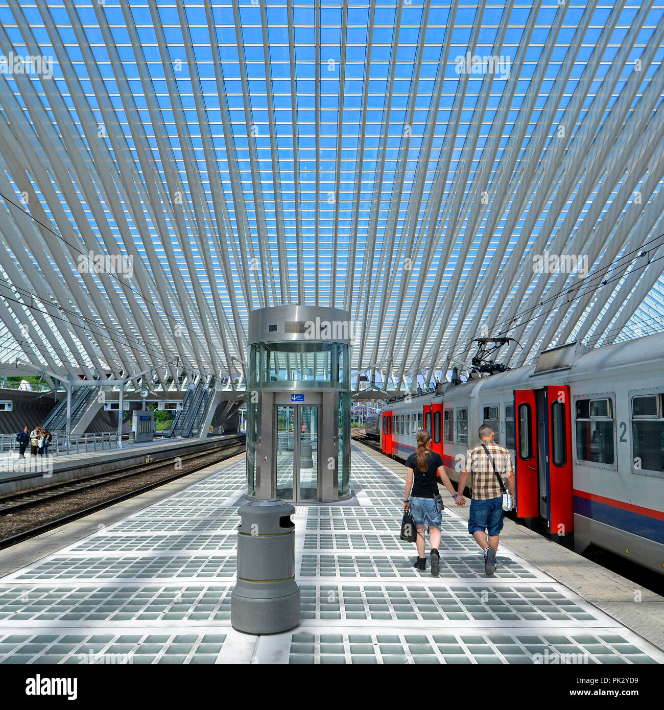 Young couple man & woman walking alone holding hands long train station platform Liège Belgium modern building glass roof ceiling blue sky summer day - Stock Image