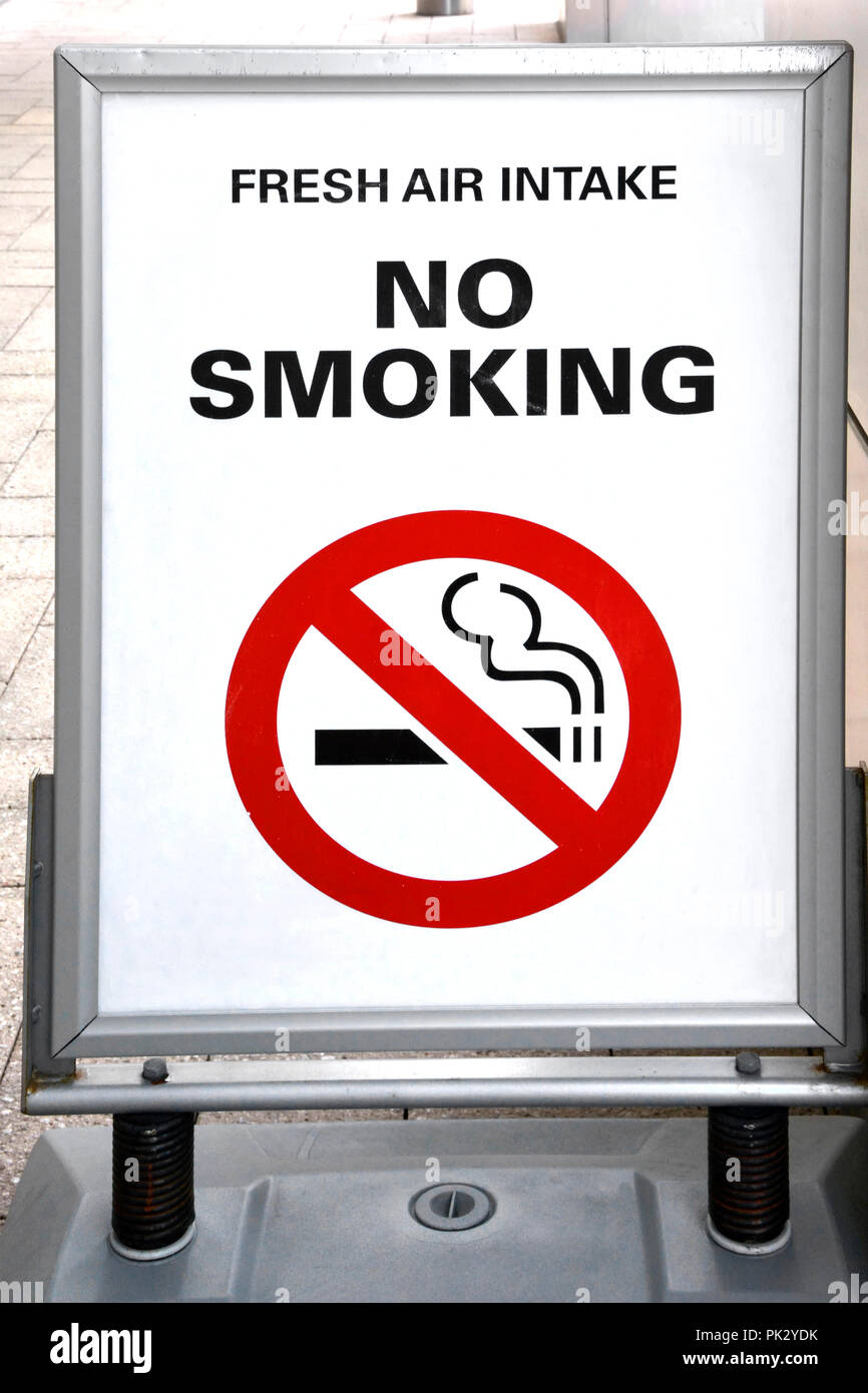 No smoking sign & icon at fresh air intake exterior of office building regulation of public behaviour outside a legally regulated indoor workplace UK - Stock Image