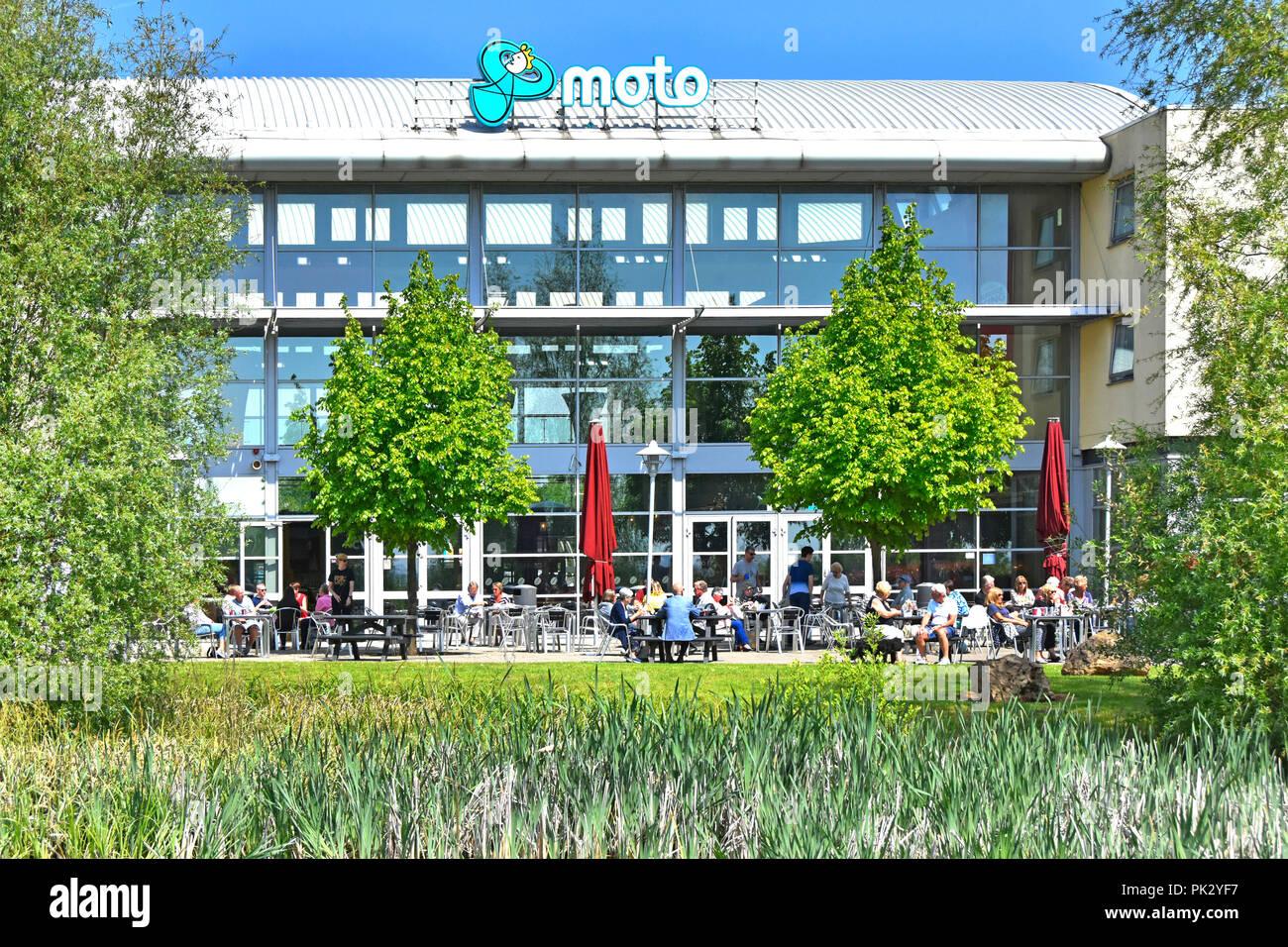 Moto Hospitality M1 motorway services logo & people break journey eating outdoor back of fast food restaurant block Donington Park Leicestershire uk - Stock Image
