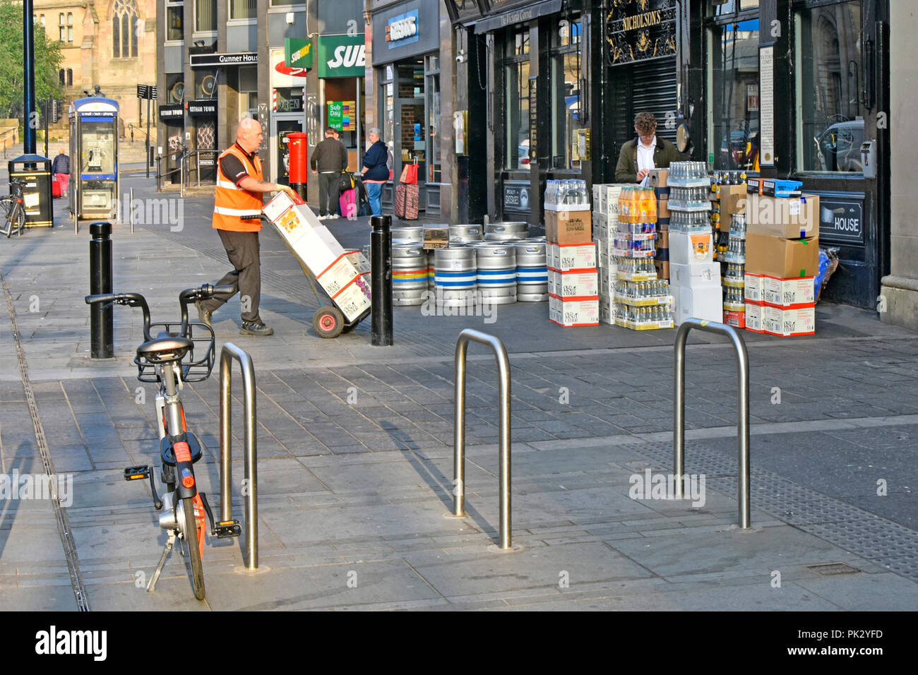 City street scene drayman with trolley makes early morning beer barrels & drink supply chain delivery outside pub Newcastle upon Tyne and Wear England - Stock Image