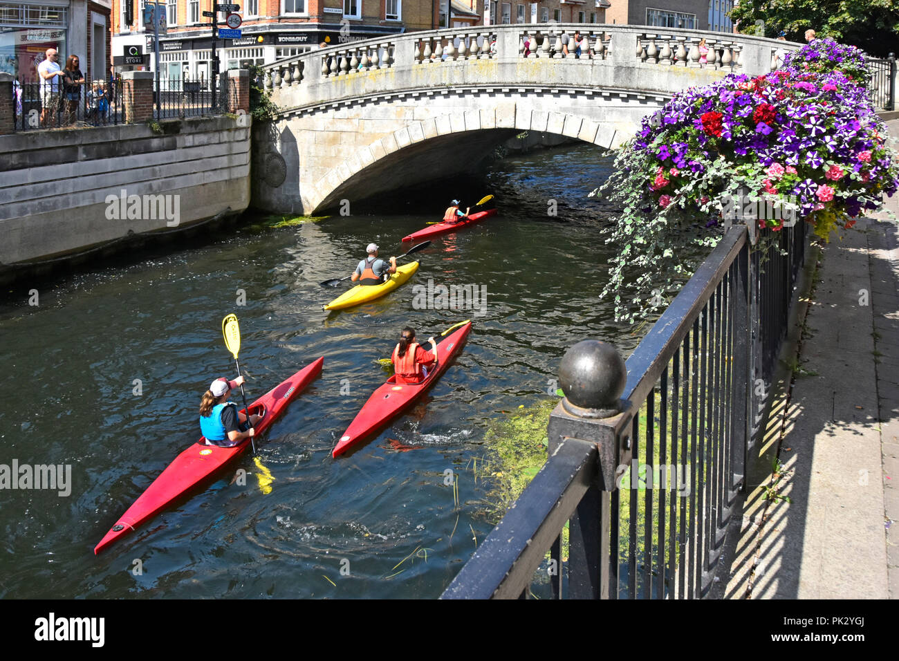Kayak boats & group of four enthusiastic people passing under stone bridge Kayaking along River Can in Chelmsford town centre Essex England UK - Stock Image